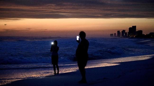 Orang-orang mengunjungi pantai sembari menunggu kedatangan badai Michael di pantai Panama City, Florida. (AFP/Brendan Smialowski)