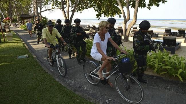Tamu asing mengendarai sepeda melewati para petugas keamanan wilayah laut dekat dengan lokasi Pertemuan Tahunan IMF-World Bank 2018.(AFP PHOTO/SONNY TUMBELAKA).