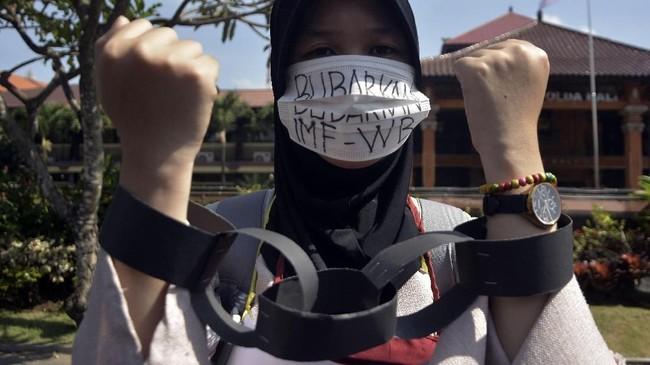 Peserta aksi yang tergabung dalam Gerakan Rakyat Menentang IMF-World Bank melakukan unjuk rasa di depan Polda Bali. (ANTARA FOTO/Fikri Yusuf).