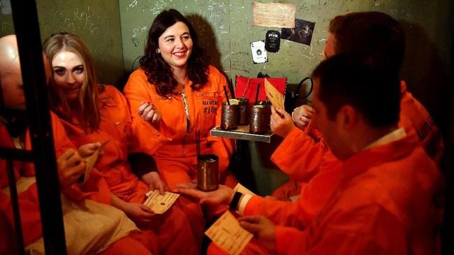 Di Alcotraz, pengunjung bakal dipinjami seragam oranye narapidana dan nomor tahanan. Bak narapidana, pengunjung akan berpura-pura menyelundupkan botol minuman ke dalam sel. (Photo by BEN STANSALL/AFP)