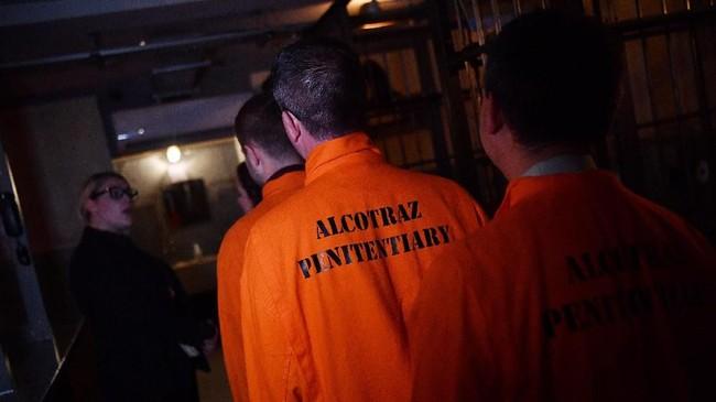Seragam oranye narapidana, sel menyeramkan, dan sipir yang beringas rasanya bukan cara ideal untuk menikmati malam di akhir pekan. Namun, itu tak berlaku bagi bar Alcotraz di London, Inggris. (Photo by BEN STANSALL/AFP)