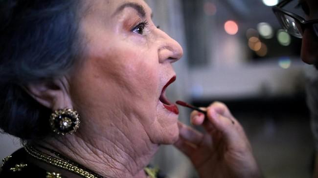 Bak model, nenek-nenek itu berjalan di catwalk dengan pelan dan terkadang harus dibantu. (REUTERS/Corinna Kern)