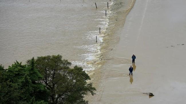 Warga setempat sudah mulai khawatir melihat hujan deras yang mengguyur di wilayah rumah mereka. (AFP Photo/Sylvain Thomas)