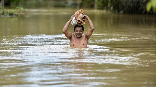 Banjir menerjang sejumlah daerah di Aceh Jaya, Aceh setelah hujan lebat yang turun kemarin (16/10). Banjir mencapai dada orang dewasa. (CHAIDEER MAHYUDDIN / AFP)