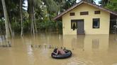 Sementara sejumlah warga diungsikan masih ada warga yang bertahan. Tampak seorang bocah malah bermain menikmati banjir di depan rumahnya. (Photo by CHAIDEER MAHYUDDIN / AFP)