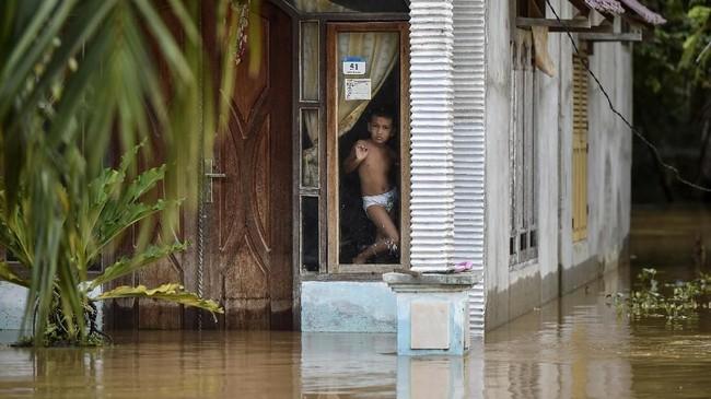 Pergerakan warga terbatas karena banjir. Sebagian warga memilih tetap berada di rumah mereka saat banjir datang.(CHAIDEER MAHYUDDIN / AFP)