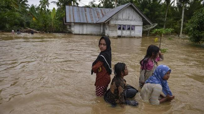 Banjir membuat jalan terputus dan hanya bisa ditempuh menggunakan perahu. Warga yang rumahnya terendam dievakuasi ke tempat aman.(Photo by CHAIDEER MAHYUDDIN / AFP)