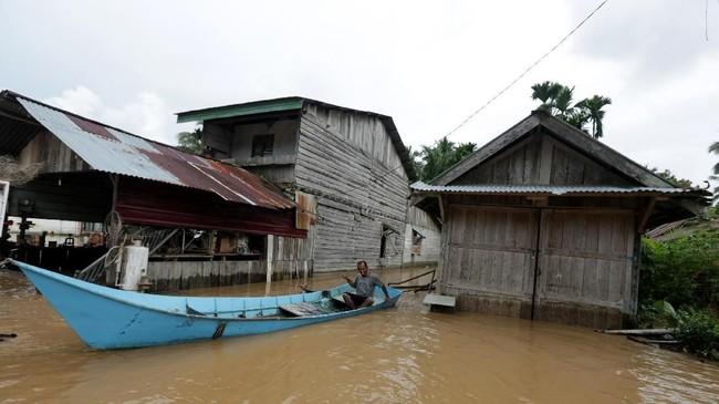Tingginya genangan air membuata warga menggunakan perahu untuk melintasi banjir. (ANTARA FOTO/Irwansyah Putra)