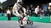 Pebalap Angel Nieto Team Alvaro Bautista melakukan wheelie dalam balapan sepeda motor mini. (REUTERS/Toru Hanai)