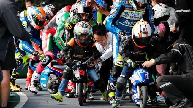 Pebalap Reale Avintia Racing Xavier Simeon (kanan) dan Hafizh Syahrin (tengah) jelang balapan motor mini yang merupakan salah satu kegiatan promosi jelang MotoGP Jepang. REUTERS/Toru Hanai