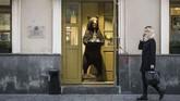 Di Moskow, seorang perempuan berjalan melewati toko yang di depan pintu masuknya terdapat boneka beruang yang sedang menawarkan vodka. (Photo by Mladen ANTONOV / AFP)
