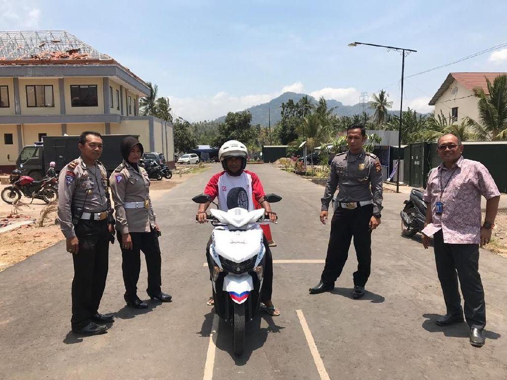 Moh Harsono Pemimpin Bank BRI Cabang Mataram, Lombok (kanan) memberikan mock-up Surat Izin Mengemudi (SIM) kepada masyarakat yang mengajukan permohonan pembuatan SIM Online di Gerai SIM Keliling Kepolisian Resort Lombok. Foto: dok. BRI