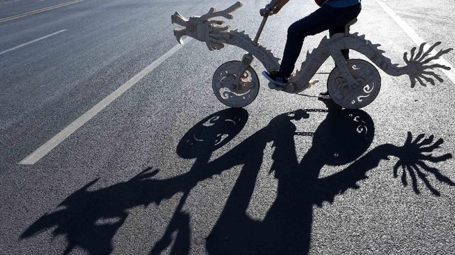 Di Tieling, Provinsi Liaoning, China, Sun Chao menunggangi sepeda berbentuk naga yang ia bikin sendiri menggunakan batang eskrim. (REUTERS/Stringer)