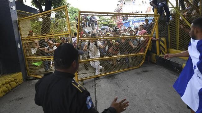 Beberapa imigran merusak pagar di perbatasan. Polisi menyebut beberapa petugas mereka juga mengalami luka-luka dalam kericuhan itu.(Photo by Pedro Pardo / AFP)