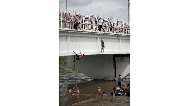 Imigran lain nekat terjun ke sungai Suchiate, berenang untuk mendapat tumpangan perahu. Lainnya berbalik kembali ke Guatemala.(REUTERS/Ueslei Marcelino)