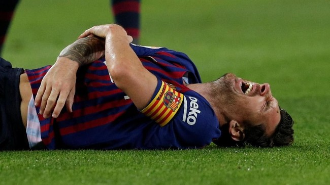 Lionel Messi memegang tangan kanan dan mengerang kesakitan setelah terjatuh usai berduel dengan pemain Sevilla Franco Vazquez. (REUTERS/Albert Gea)