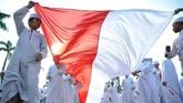 Sejumlah santri membentangkan bendera Merah Putih saat kirab memperingati Hari Santri Nasional di halaman kantor DPRD Sumsel, Palembang, Sumsel, Sabtu (20/10). (ANTARA FOTO/Feny Selly)