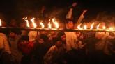Sejumlah santri menonton pertandingan sepak bola api di area pondok pesantren Lirboyo, Kota Kediri, Jawa Timur, Kamis (18/10) malam. Kegiatan yang diselenggarakan Nahdlatul Ulama (NU) di lingkungan pondok pesantren terbesar se-Jawa Timur tersebut guna mensosialisasikan Hari Santri Nasional. (ANTARA FOTO/Prasetia Fauzani)