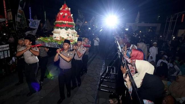 Warga menyaksikan tumpeng raksasa diarak saat Istighosah Akbar di Masjid Nasional Al Akbar, Surabaya, Jawa Timur, Kamis (18/10) malam. Kegiatan bertema Untuk Indonesia Aman, Damai dan Sejuk itu untuk menyambut Hari Santri Nasional. (ANTARA FOTO/Didik Suhartono)
