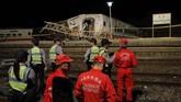 Beberapa pekerja memberikan pertolongan pertama kepada orang yang terluka, sementara pekerja lain menggunakan alat berat untuk mengangkat mobil yang hancur di dekat rel kereta. (AFP Photo/Daniel Shih)