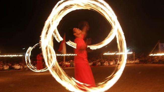 Santri memainkan toya api di pondok pesantren Lirboyo, Kota Kediri, Jawa Timur, Kamis (18/10) malam. Kegiatan di lingkungan pondok pesantren terbesar se-Jawa Timur dalam rangka memperingati Hari Santri Nasional. (ANTARA FOTO/Prasetia Fauzani)