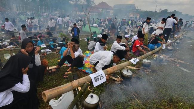 Sejumlah santri mengikuti lomba memasak nasi liwet saat memperingati Hari Santri Nasional di kawasan Kantor Setda Kabupaten Tasikmalaya, Jawa Barat, Sabtu (20/10). Lomba yang diikuti 10 ribu santri dari 700 pondok pesantren se-Tasikmalaya itu memecahkan rekor MURI kategori memasak nasi liwet terbanyak. (ANTARA FOTO/Adeng Bustomi)
