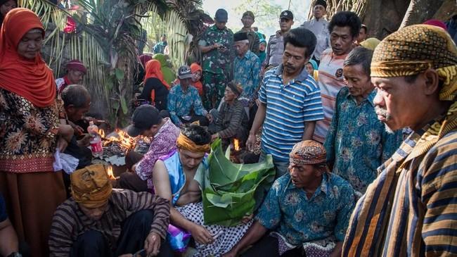 Banyak warga yang sengaja menunggu di depan rumah untuk mendapat lemparan dari sesaji makanan tersebut berharap mendapat berkah.