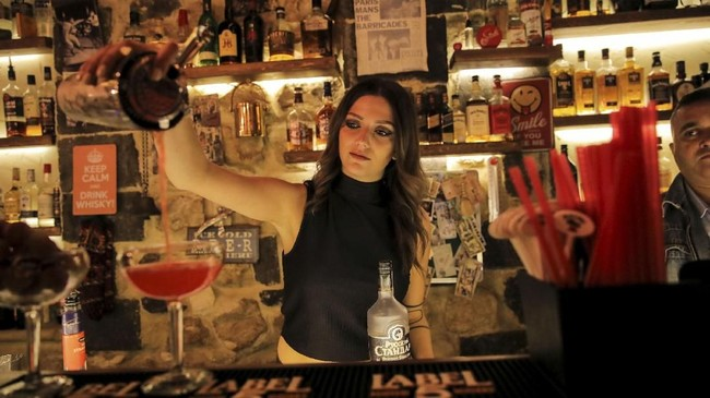 Dana (24) seorang bartender, menuangkan minuman di sebuah bar di kota tua Damascus,Suriah. (REUTERS/Marko Djurica)