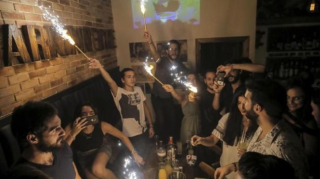 Orang-orang juga merayakan ulang tahundi bar di kota tuadiDamascus, Suriah.Wargajuga keluar ke jalan-jalan untuk bermain gitar atau sekedar menghabiskan waktu di kafe (REUTERS/Marko Djurica)