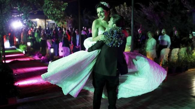 Pengantin pria dibawa di pundak teman-teman dan keluarganya, sementara orang-orang bertepuk tangan di sekitarnya. ia pun mengayunkan sang pengantin ke dalam pelukannya.(REUTERS/Marko Djurica)