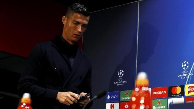 Cristiano Ronaldo sedang asyik memainkan telepon genggam sebelum konferensi pers dimulai. Ronaldo masih menjalin kontak dengan mantan manajer Manchester United, Sir Alex Ferguson. (Reuters/Jason Cairnduff)