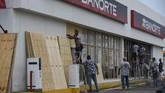 Jelang badai, para pekerja mulai melindungi toko-toko mereka dengan panel kayu di pelabuhan Mazatlan di wilayah Sinaloa, Meksiko (ALFREDO ESTRELLA / AFP)