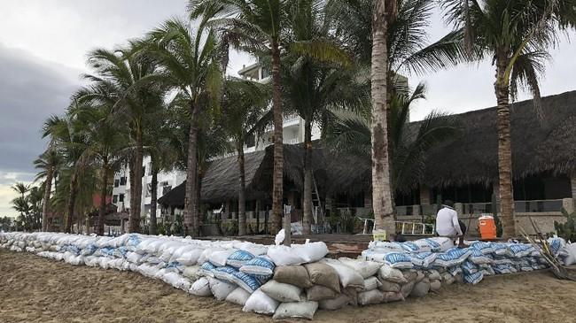 Tempat-tempat yang berada di pinggir pantai juga melindungi diri dari gelombang tinggi dengan menempatkan kantong-kantong pasir sebagai benteng. (Daniel SLIM / AFP)