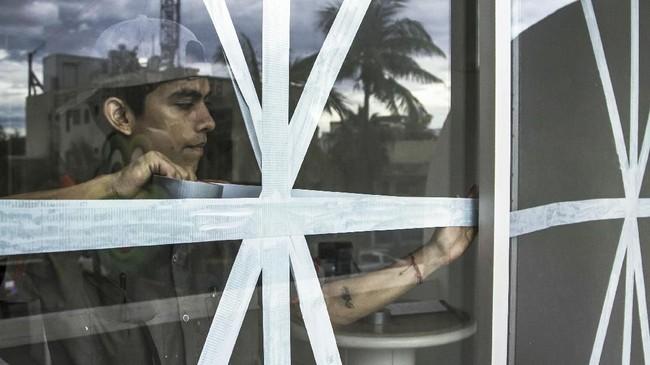 Pekerja menggunakan selotip untuk melindungi jendela dari hurikan Willa (RASHIDE FRIAS / AFP)