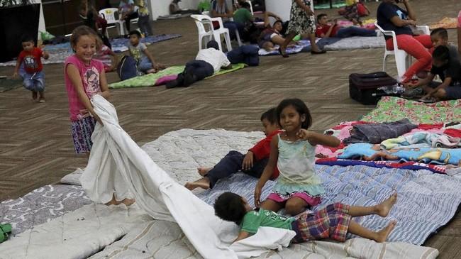 Para penduduk yang mengungsi khawatir rumah mereka tak kuat menahan terpaan badai dan menimpa mereka. (REUTERS/Henry Romero)