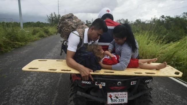 Masih belum diketahui berapa total korban akibat badai ini. Seorang anak kecil yang terluka tengah diantar orang tuanya dengan motor dari kampung nelayan yang aksesnya masih tertutup(Photo by Alfredo ESTRELLA / AFP)