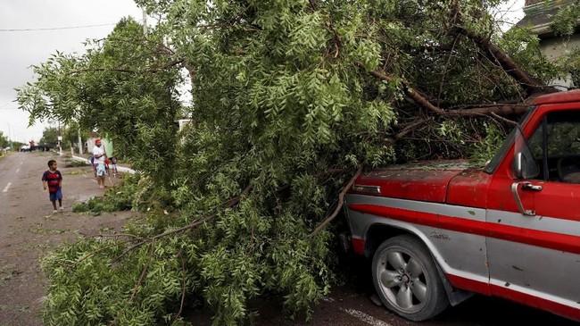 Mereka khawatir akan tertimpa pohon atau atap rumah mereka sendiri jika nekat bertahan di dalam rumah. (REUTERS/Henry Romero)