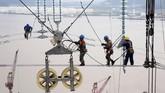 Para pekerja berada di atas kabel listrik yang menghubungkan menara transmisi di Zhoushan, Provinsi Zheijang, China. (REUTERS/Stringer)