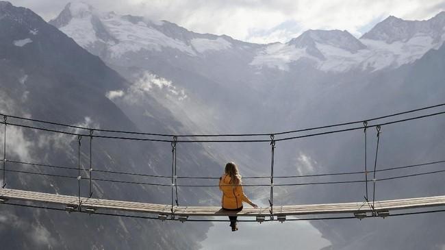 Pada hari yang cerah di musim gugur, seorang perempuan duduk di jembatan berayun yang terbentang di atas bendungan Schlegei, dekat desa Ginzling, Austria. (REUTERS/Lisi Niesner)