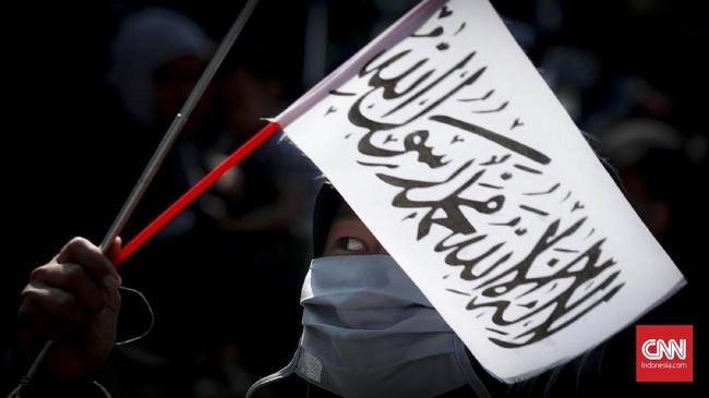Dalam aksi ini, massa membawa bendera berwarna hitam dan putih yang diyakni sebagai panji rasul yang memuat kalimat tauhid. (CNNIndonesia/Safir Makki)