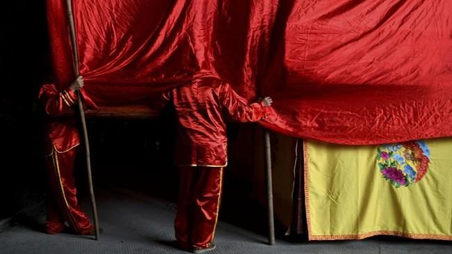 Pekerja terlihat di belakang tirai merah di suatu panggung di dalam gua di Taman Geologi Shihai di Yibin, Provinsi Sichuan. Panggung itu menampilkan opera tradisional. (REUTERS/Stringer)