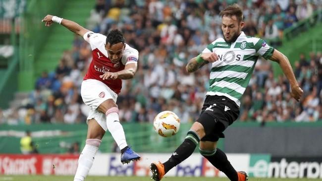 Penyerang Arsenal Pierre-Emerick Aubameyang melepaskan tendangan melewati pemain Sporting Lisbon Nemanja Gudelj. Arsenal sempat kesulitan mencetak gol di babak pertama. (Action Images via Reuters/Peter Cziborra)