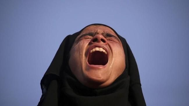 Seorang gadis menangis ketika melihat tubuh Mehraj-ud-Din Bangroo, seorang tersangka militan, yang diduga tewas dalam baku tembak dengan pasukan pengamanan India. Proses pemakaman Mehraj-ud-Din Bangroo dilangsungkan di Srinagar. (REUTERS/Danish Ismail)