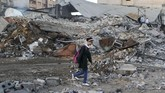 Seorang siswi sekolah Palestina berjalan melewati salah satu area yang terkena dampak serangan roket Israel. Hujan roket ini terus menjadi pemandangan keseharian warga Palestina yang telah terusir dari kampung halamannya sendiri. (REUTERS/Mohammed Salem)