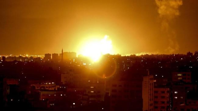 Sebuah ledakan terjadi akibat roket yang diluncurkan Israel ke kota Gaza pada Sabtu (27/10) pagi. Hujan roket ini merupakan balasan atas puluhan serangan Gaza ke Israel pada satu hari sebelumnya. (Photo by MAHMUD HAMS / AFP)