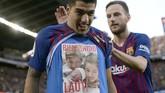 Luis Suarez menunjukkan foto anak ketiganya yang baru lahir sebagai pertanda gol tersebut ia persembahkan kepada sang anak. (Photo by Josep LAGO / AFP)