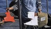 Prajurit TNI AL menunjukan serpihan yang diduga dari pesawat Lion Air JT610 saat pencariaan menggunankan KRI Kobra di perairan Karawang, Jawa Barat, Senin (29/10). (ANTARA FOTO/Hafidz Mubarak A)