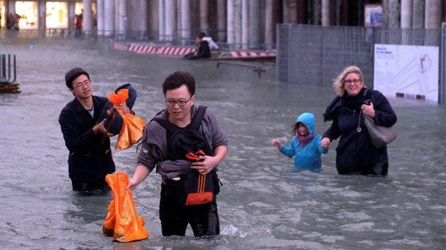Para turis dan warga setempat terpaksa menerjang genangan air setinggi pinggang untuk beraktivitas. (Reuters/Manuel Silvestri)
