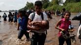 Proses verifikasi data yang lama membuat ribuan imigran jengah hingga akhirnya memutuskan untuk menyeberangi Sungai Suchiate dengan berenang. (Reuters/Carlos Garcia Rawlins)