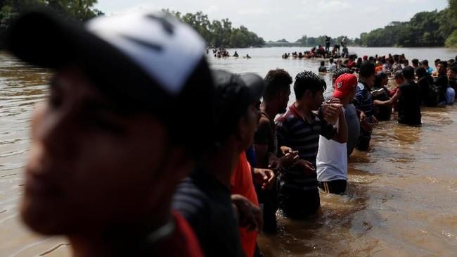 Setelah menempuh perjalanan panjang dari tanah airnya, para imigran tiba di perbatasan Guatemela dan Meksiko pada Minggu (28/10), di mana mereka harus menyeberangi Sungai Suchiate. (Reuters/Carlos Garcia Rawlins)